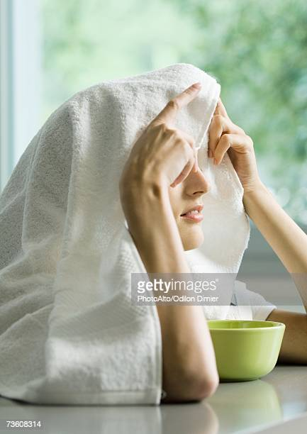 Woman with face over bowl and towel over head