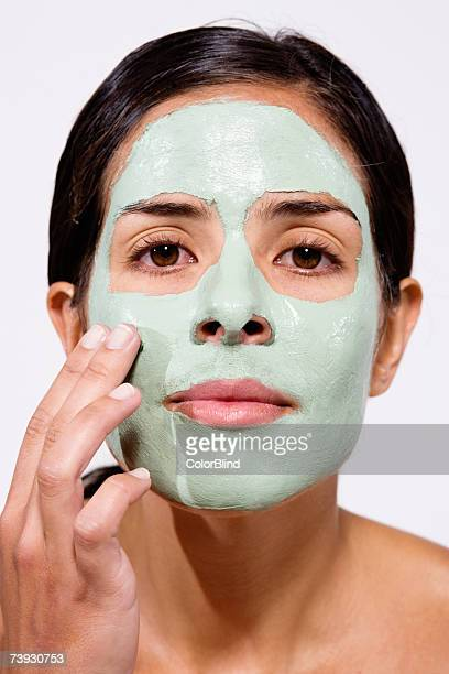 Woman with face pack on, portrait