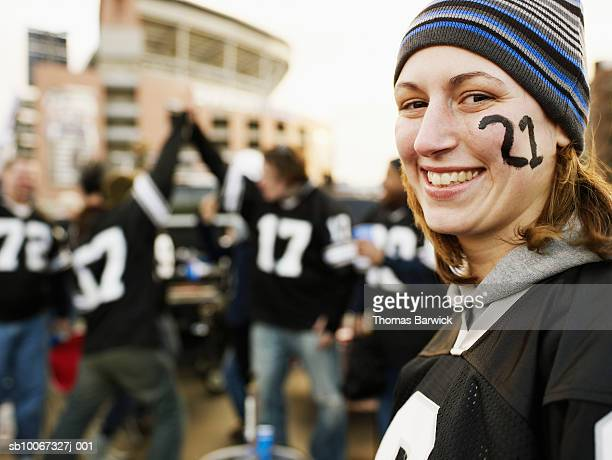 Woman with face paint smiling at tailgate party, friends in background