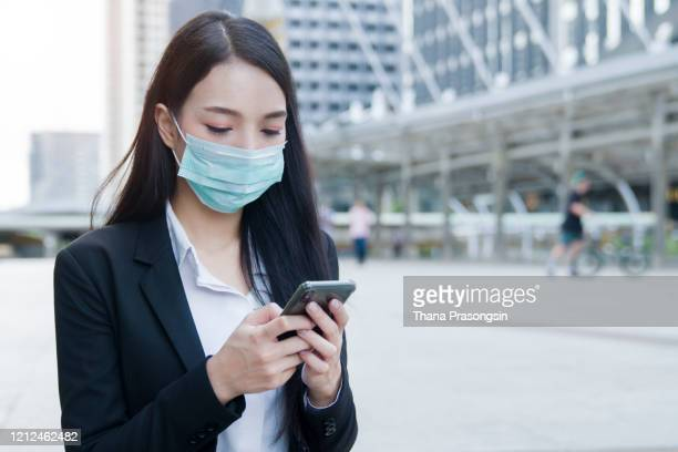 woman with face protective mask - woman texting stockfoto's en -beelden