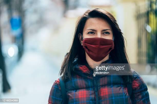 frau mit gesichtsschutzmaske - grippeschutzmaske stock-fotos und bilder