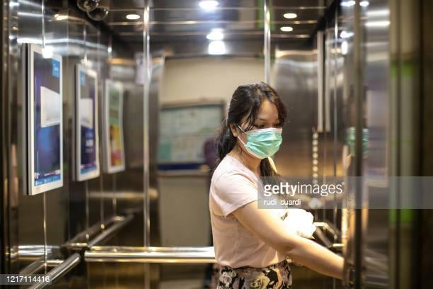 mulher com máscara protetora facial - elevador - fotografias e filmes do acervo