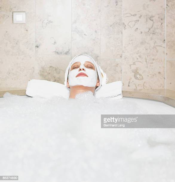 Woman (36y) with facial mask in bathtub