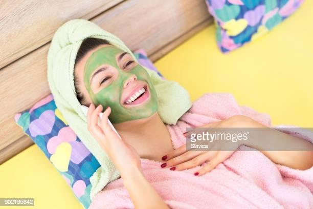 Femme avec masque facial sur le visage en parlant au téléphone