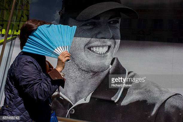 Woman with fan shielding her face from sunchine passes a Nike retail poster of Northern Irish golfer Rory McIlroy in central London The scene has a...