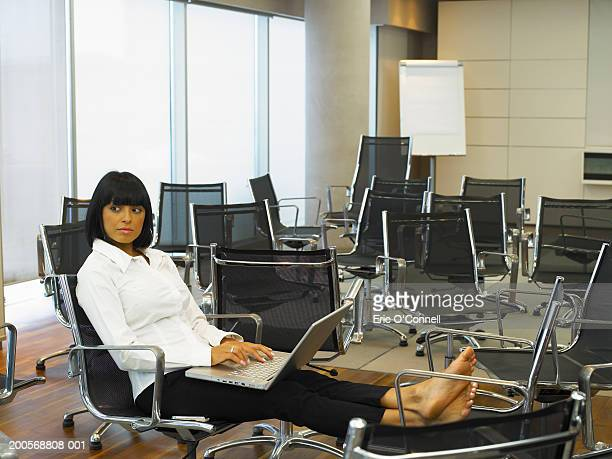Woman with feet on chair using laptop in room full of chairs