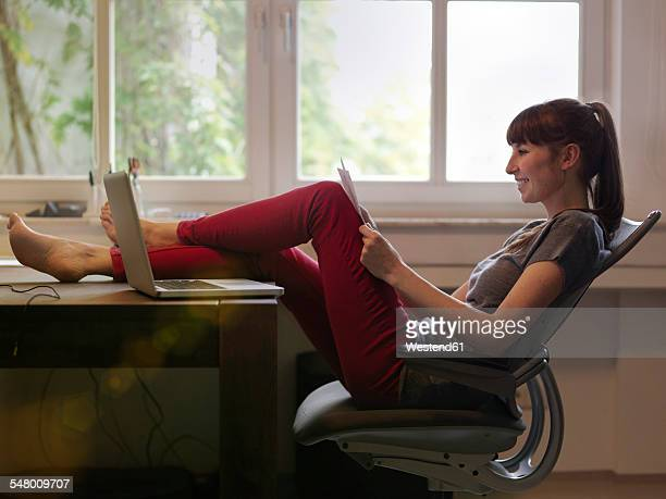 woman with feet on desk reading paper - barefoot redhead stock photos and pictures