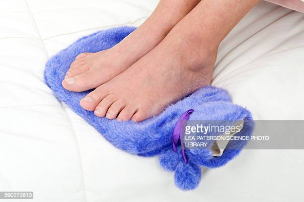 Woman with feet on hot water bottle