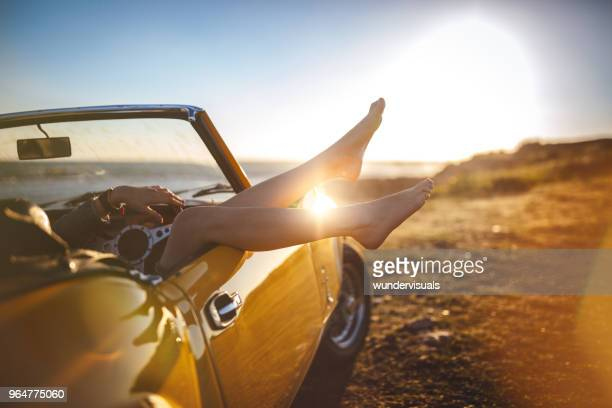 woman with feet sticking out convertible car relaxing on holidays - beach fun stock pictures, royalty-free photos & images