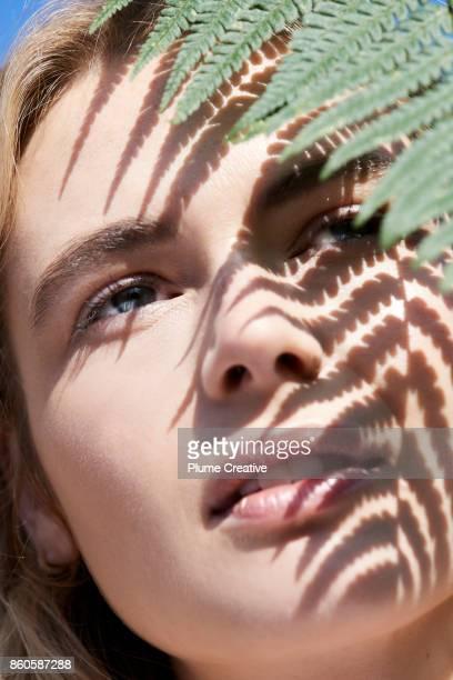 woman with fern frond over face - natürliche schönheit personen stock-fotos und bilder