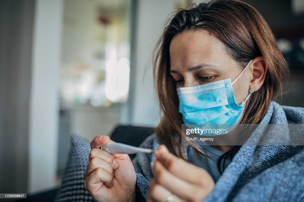 Woman with fever symptoms sitting on sofa and looking at thermometer : Stock Photo