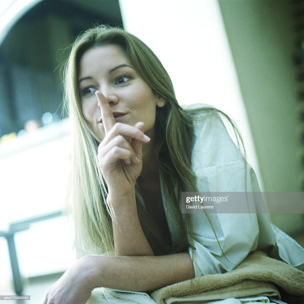 Woman with finger in front of lips : Stockfoto