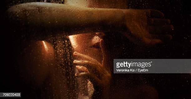 woman with finger on lips bathing seen through glass - ksi stock photos and pictures