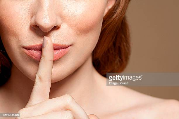 Woman with finger on lips, close up