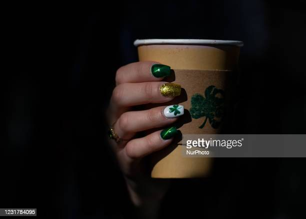 Woman with fingernails decorated for St. Patrick's having a coffee outside the Irish Potato Cake Company restaurant in Dublin's city center on St....
