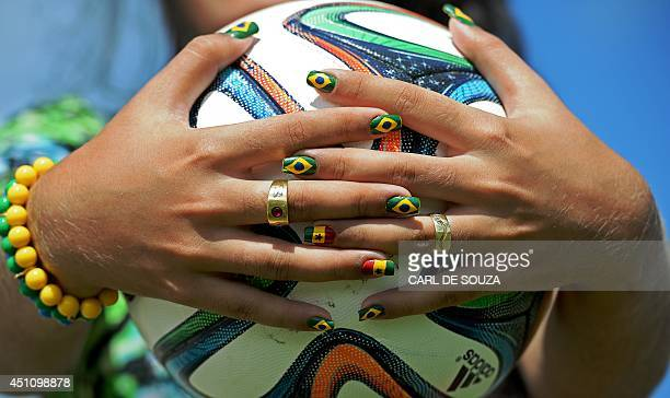A woman with fingernails painted with the flag symbols of Brazil and Ghana holds the official World Cup ball Brazuca at the Rei Pele stadium in...