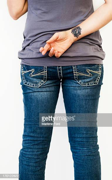 Woman with fingers crossed behind back