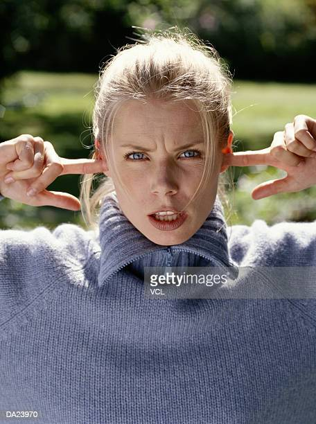 woman with fingers in ears, portrait - fingers in ears stock pictures, royalty-free photos & images