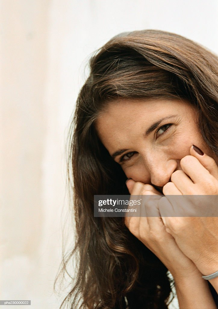 Woman with fists to mouth, portrait. : Stockfoto