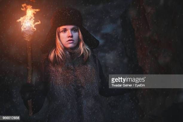 woman with flaming torch in cave at night during winter - cave fire stock photos and pictures