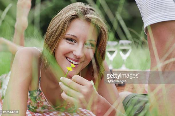 Woman with flower on picnic blanket