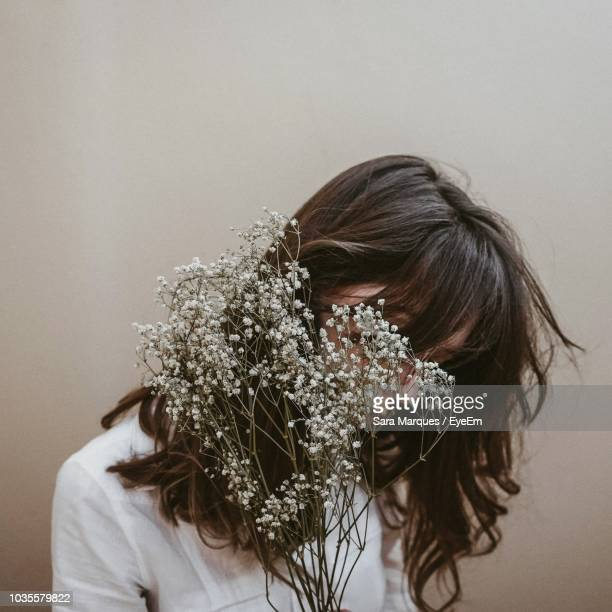 Woman With Flowers Against White Wall