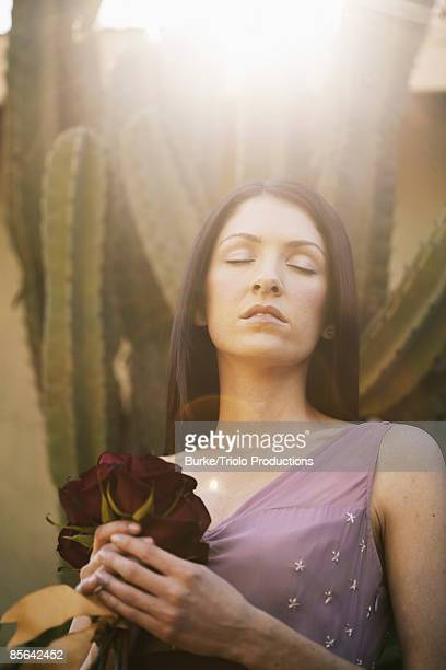 Woman with flowers by cactus