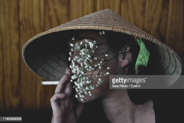 woman with flowers covering face smoking against wall - chapeau chinois photos et images de collection