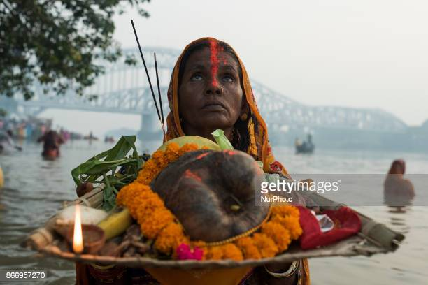 A woman with flowers fruits and oil candles for performing her evening ritual during the Chhath puja celebrations in Kolkata West Bengal on October...