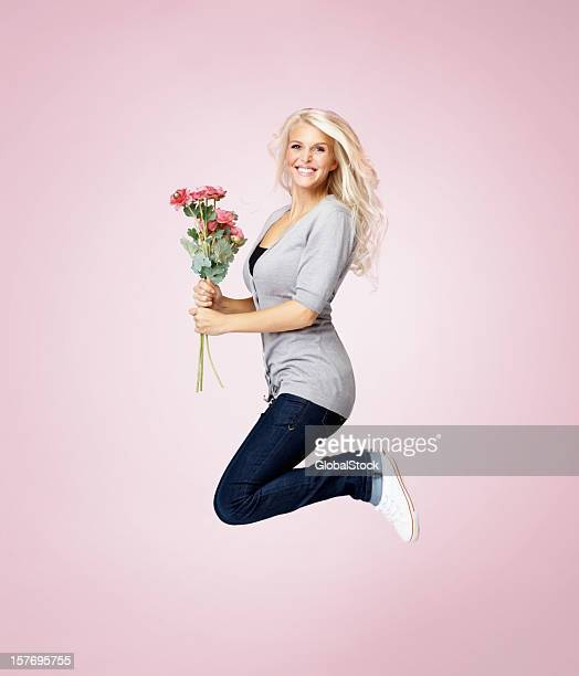 Woman with flowers jumping in joy