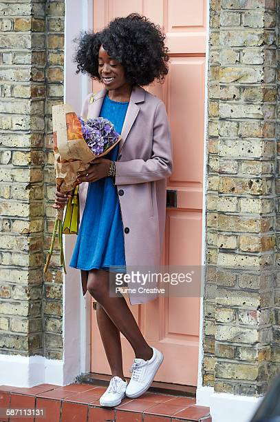 Woman with flowers standing in front of colourful door.