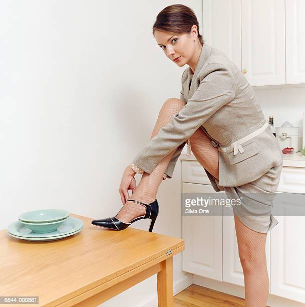 woman with foot on table - nylon feet stock photos and pictures