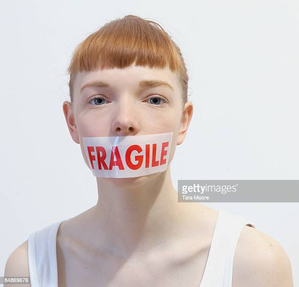 woman with fragile sticker covering mouth
