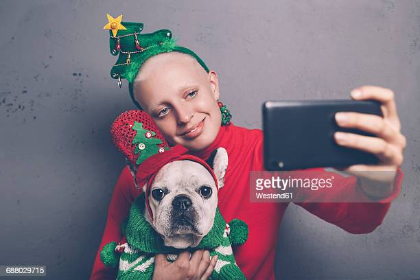 Woman with French bulldog taking selfie with smartphone at Christmas time