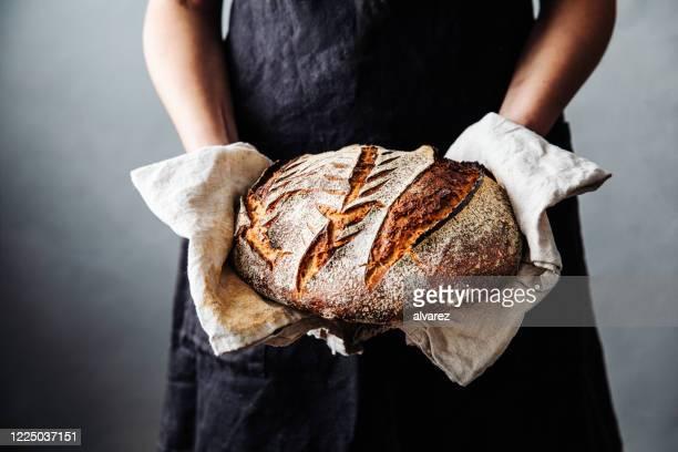 vrouw met vers gebakken zuurdesembrood in keuken - brood stockfoto's en -beelden