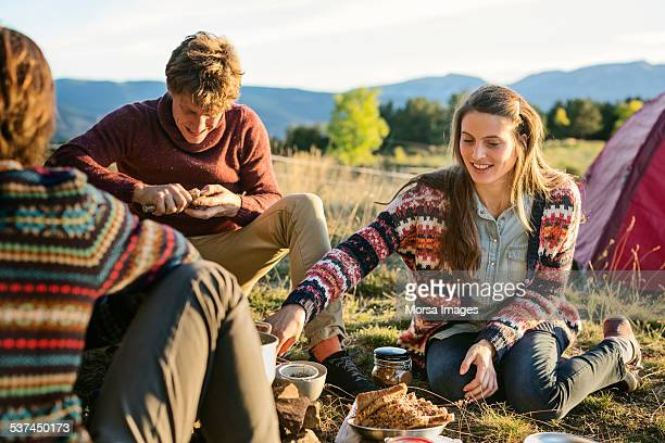 Woman with friends having breakfast at campsite