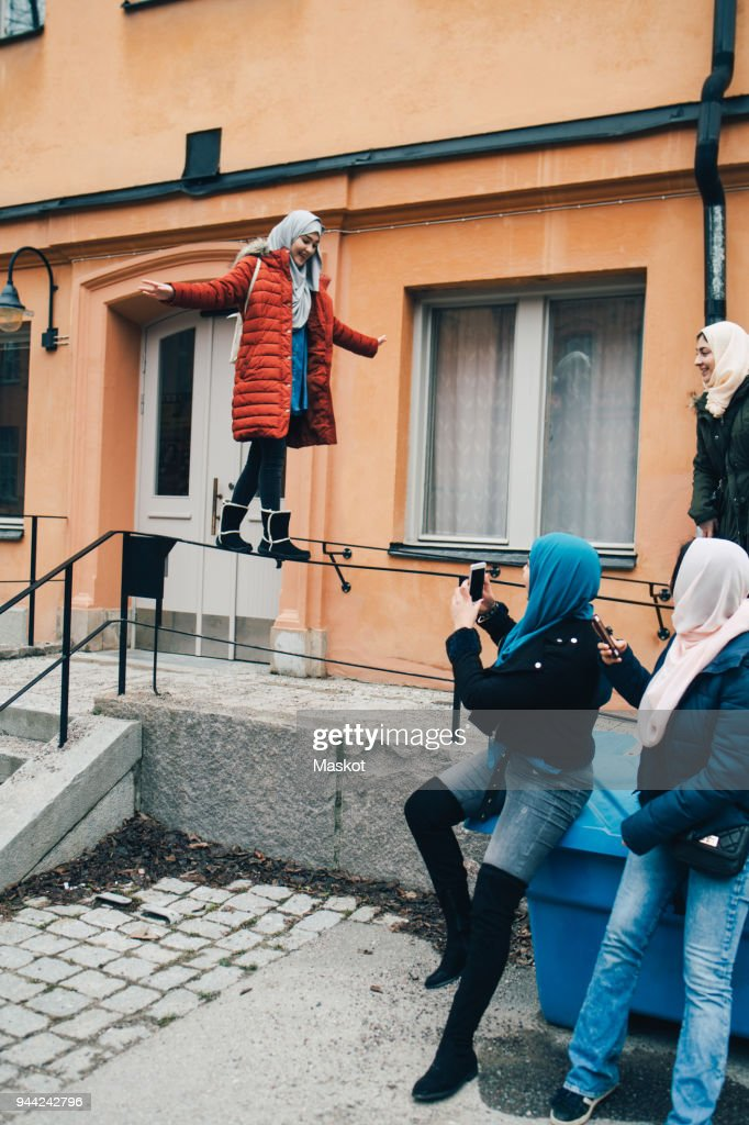 Woman with friends photographing female balancing on railing against building in city : Stock Photo