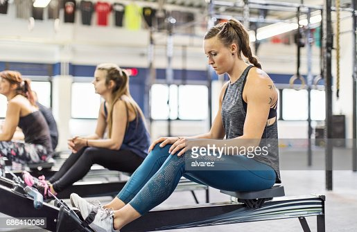 Woman with friends sitting on rowing machines