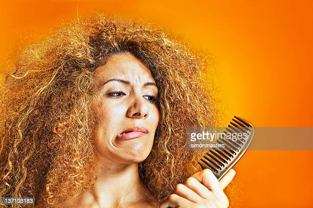 Woman with frizzy and curly hair looking at a comb
