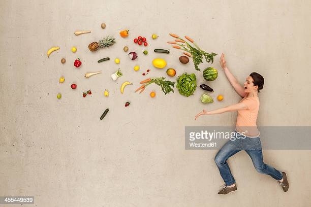 Woman with fruits and vegetables against beige background