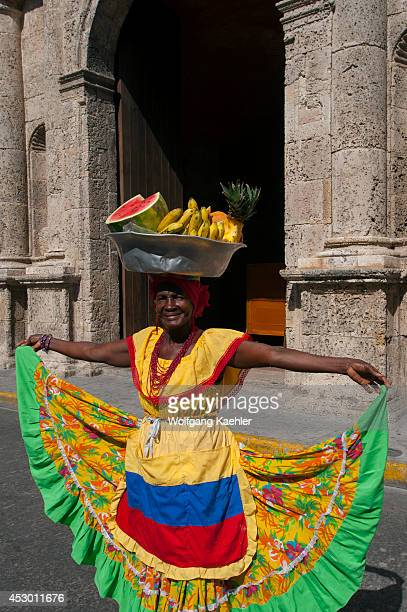 Woman with fruits in colonial costume in front of Santo Domingo Convent on Plaza Santo Domingo in Cartagena Colombia a walled city and Unesco World...