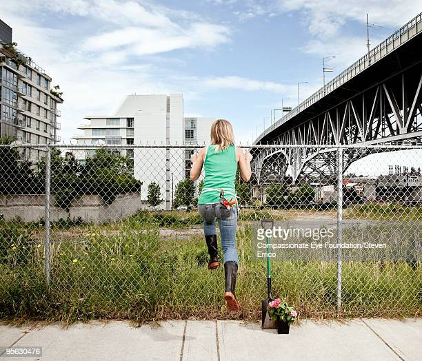 woman with gardening tools climbing over fence