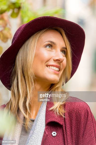 woman with garnet coat walking in the street - mid adult stock pictures, royalty-free photos & images