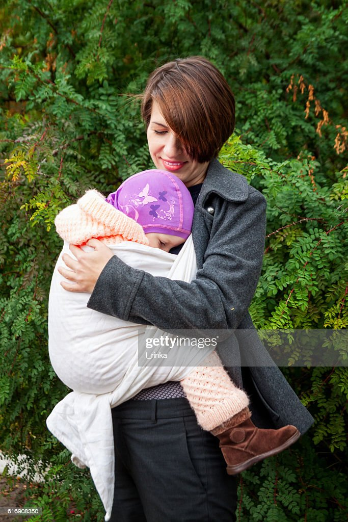 Woman with gaughter in sling : Stock Photo