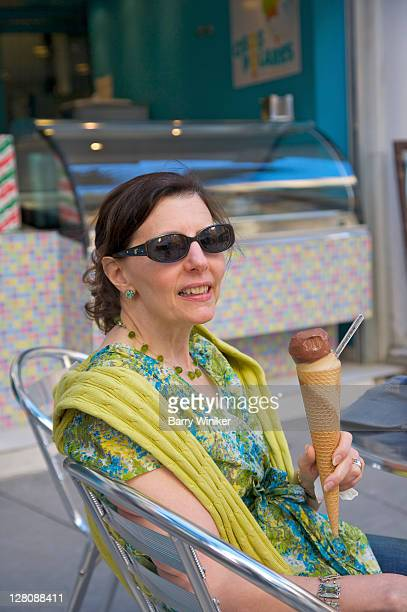 Woman with gelato in sugar cone at cafe on street of Malaga, Costa del Sol, Andalucia, Spain