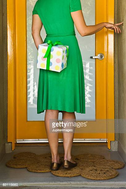 Woman with gift ringing doorbell