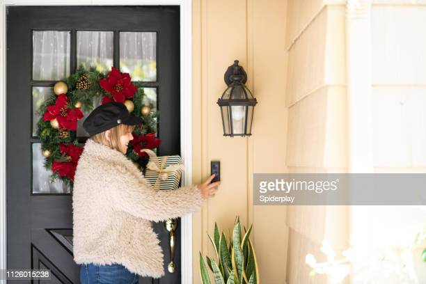 woman with gift rings doorbell - ringing doorbell stock pictures, royalty-free photos & images