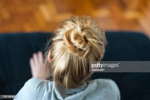 Woman with ginger hair bun sitting on sofa