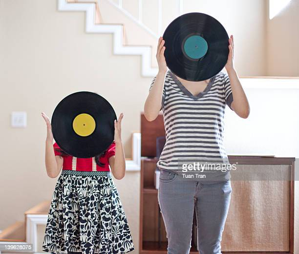 Woman with girl holding vinyl record