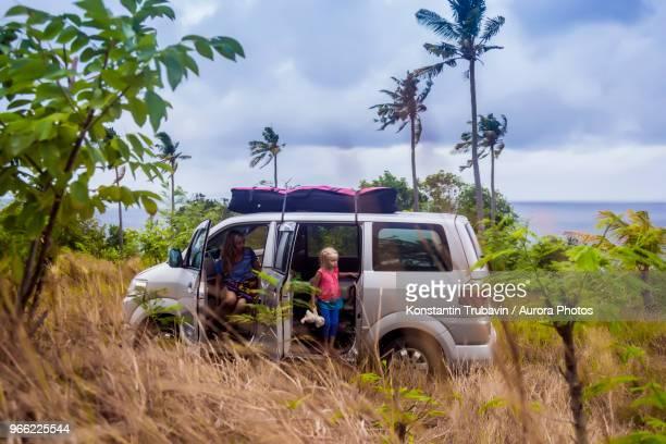 Woman with girl in car on seashore in tropical scenery, Nusa Penida, Bali, Indonesia